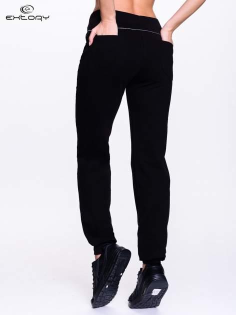 Czarne spodnie dresowe z aplikacją z dżetów PLUS SIZE                                  zdj.                                  4