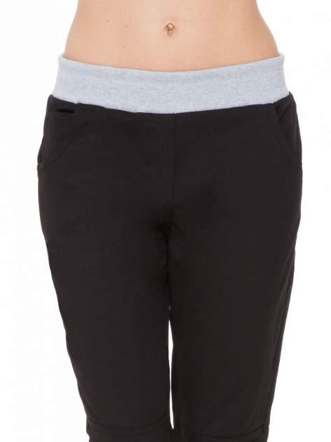 Czarne spodnie dresowe z guziczkami na nogawkach                                  zdj.                                  5