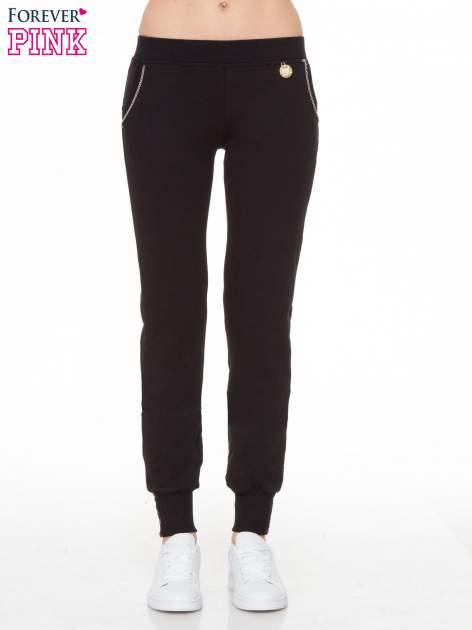 Czarne spodnie dresowe z łańcuszkami przy kieszeniach                                  zdj.                                  1