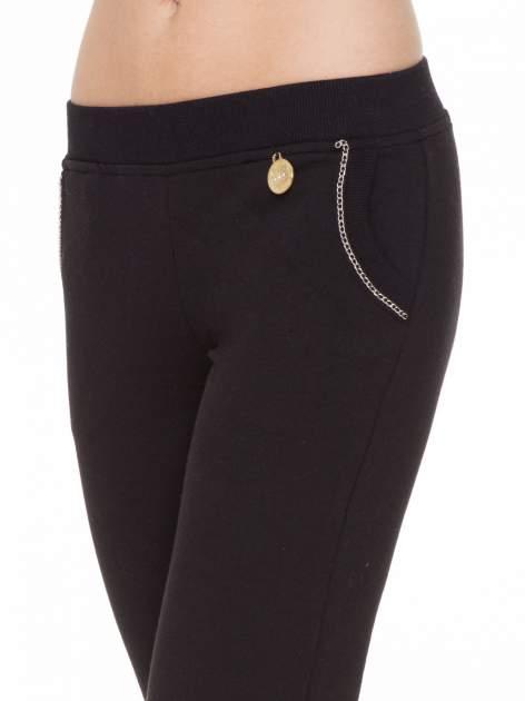 Czarne spodnie dresowe z łańcuszkami przy kieszeniach                                  zdj.                                  9