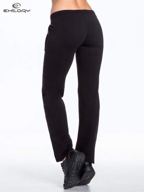 Czarne spodnie dresowe z nadrukiem kwiatów i dżetami                                  zdj.                                  2
