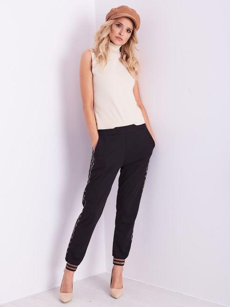 Czarne spodnie dresowe z ozdobnymi lampasami                              zdj.                              8