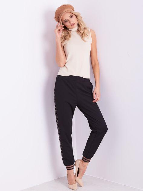 Czarne spodnie dresowe z ozdobnymi lampasami                              zdj.                              4