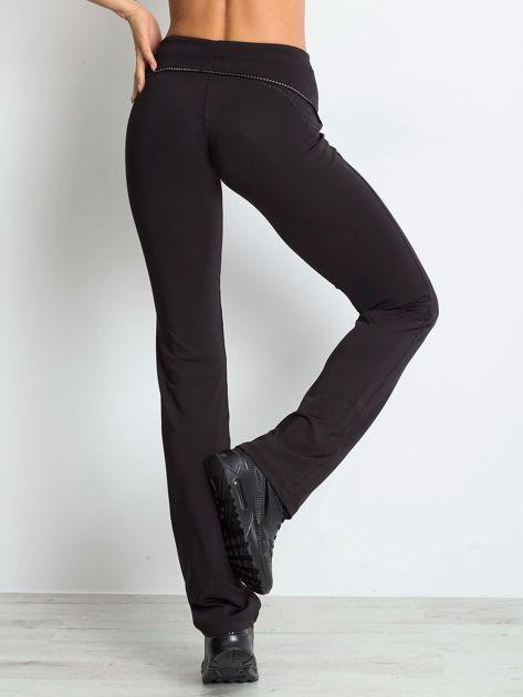 Czarne spodnie z troczkami i wzorkiem po boku                              zdj.                              2
