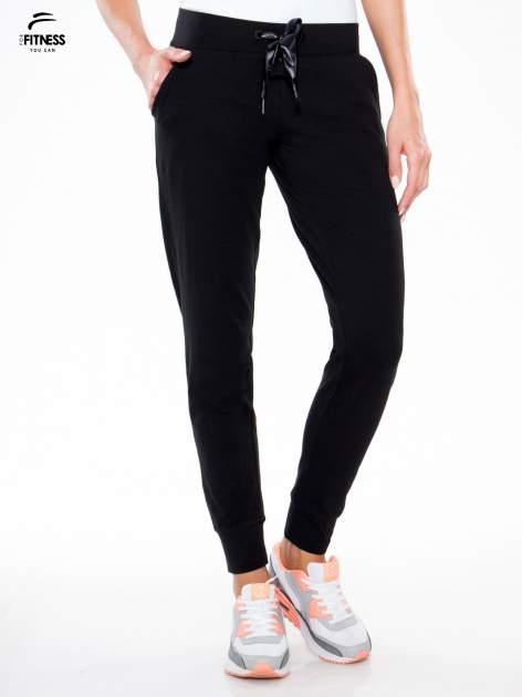 Czarne wąskie spodnie dresowe wiązane w pasie na wstążkę