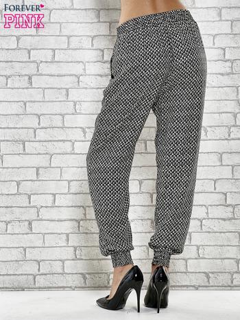 Czarne zwiewne spodnie alladynki w drobny wzór geometryczny                                  zdj.                                  4