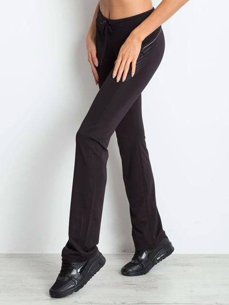 Czarnobrązowe śliskie spodnie z troczkami i wzorkiem po boku                                  zdj.                                  3