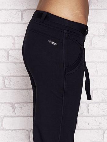 Granatowe dresowe spodnie capri z materiałowym paskiem                                  zdj.                                  5