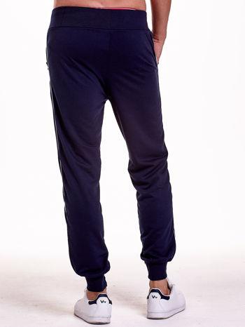 Granatowe dresowe spodnie męskie z lampasami po bokach i aplikacją                                  zdj.                                  5