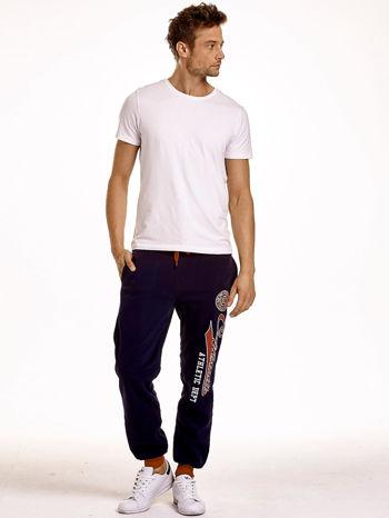 Granatowe dresowe spodnie męskie z napisem CALIFORNIA i naszywką                                  zdj.                                  4