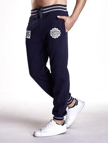 Granatowe dresowe spodnie męskie z naszywkami i kieszeniami                                  zdj.                                  2