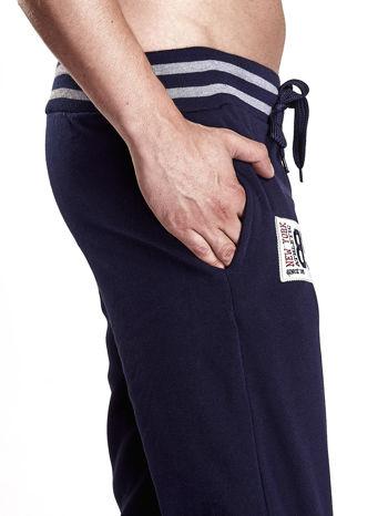 Granatowe dresowe spodnie męskie z naszywkami i kieszeniami                                  zdj.                                  5