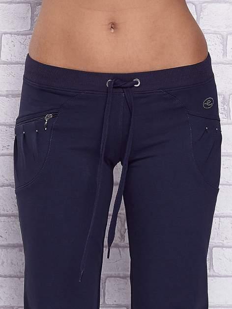 Granatowe spodnie capri z boczną kieszonką i dżetami                                  zdj.                                  4