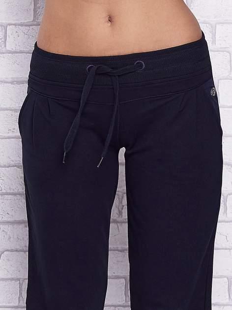 Granatowe spodnie capri z tylną kieszenią                                  zdj.                                  4