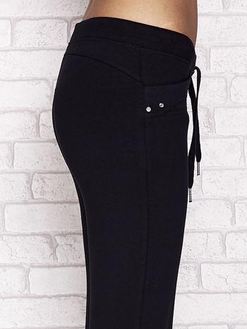 Granatowe spodnie dresowe capri z aplikacją na kieszeniach                                  zdj.                                  5
