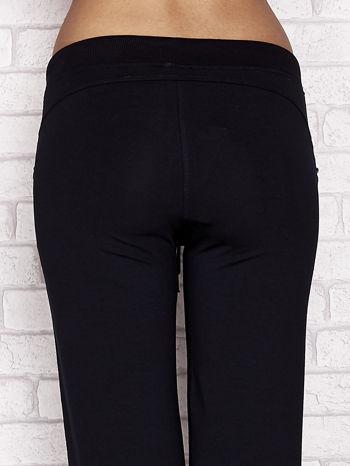 Granatowe spodnie dresowe capri z aplikacją na kieszeniach                                  zdj.                                  6