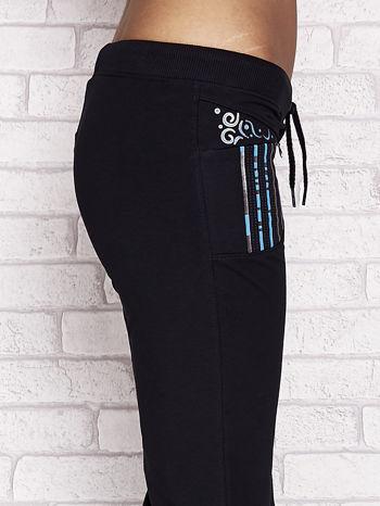 Granatowe spodnie dresowe capri z dziewczęcymi nadrukami                                  zdj.                                  5