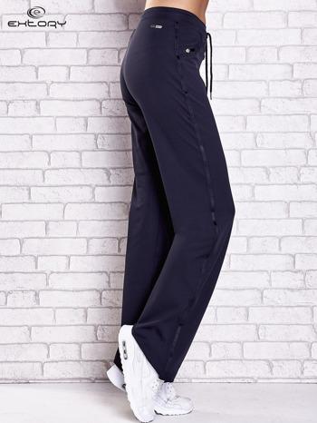 Granatowe spodnie dresowe z aplikacjami z błyszczących dżetów                                  zdj.                                  2