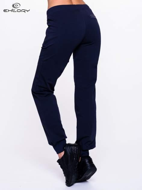 Granatowe spodnie dresowe z elastyczną gumką w pasie PLUS SIZE                                  zdj.                                  4