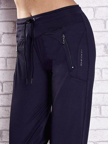 Granatowe spodnie dresowe z kieszeniami i przeszyciami                                  zdj.                                  4