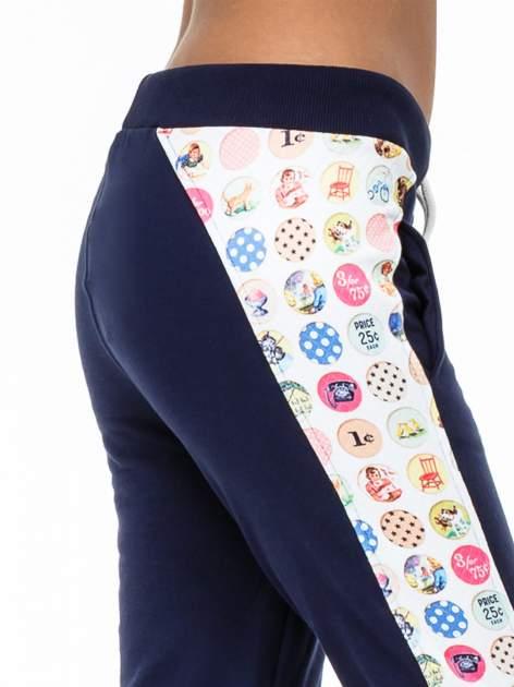 Granatowe spodnie dresowe z lampasem w znaczki                                  zdj.                                  5