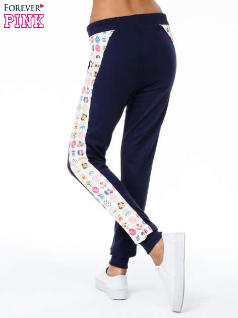 Granatowe spodnie dresowe z lampasem w znaczki                                  zdj.                                  4