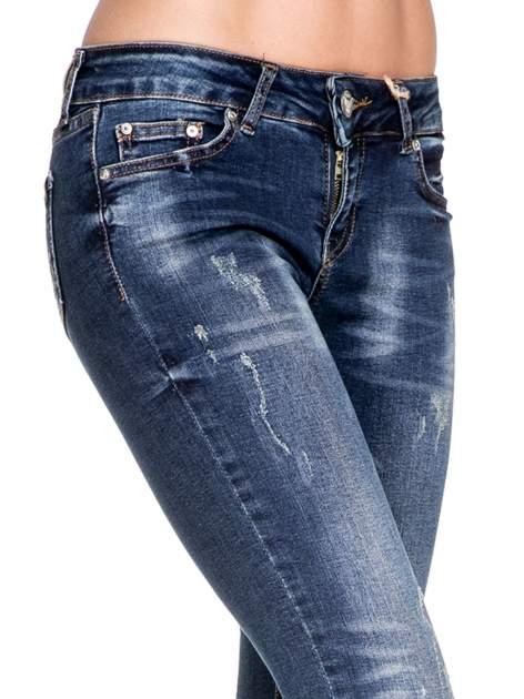 Granatowe spodnie skinny jeans z przecieraną nogawką z przodu                                  zdj.                                  7