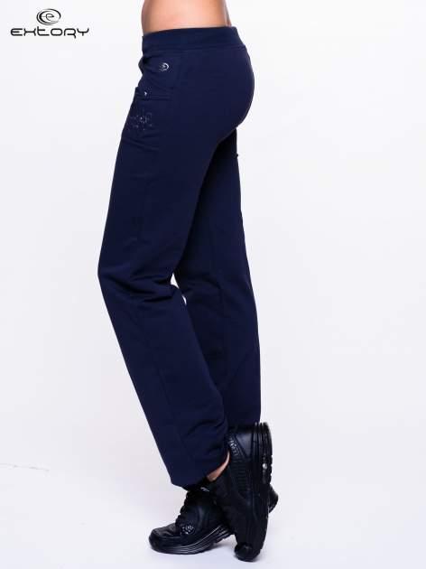 Jasnogranatowe spodnie dresowe z kwiatem z dżetami                                  zdj.                                  3