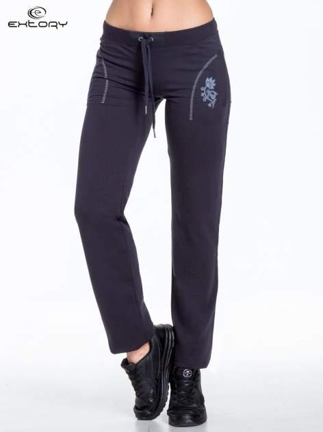 Jasnogranatowe spodnie dresowe z kwiatem z dżetami i przeszyciem                                  zdj.                                  1