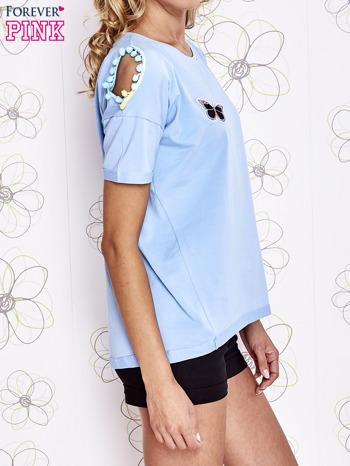 Jasnoniebieski t-shirt z naszywką motyla i pomponami                                  zdj.                                  3
