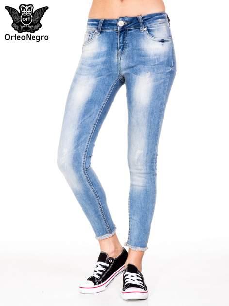 Jasnoniebieskie spodnie jeansowe rurki z poszarpaną nogawką na dole                                  zdj.                                  1