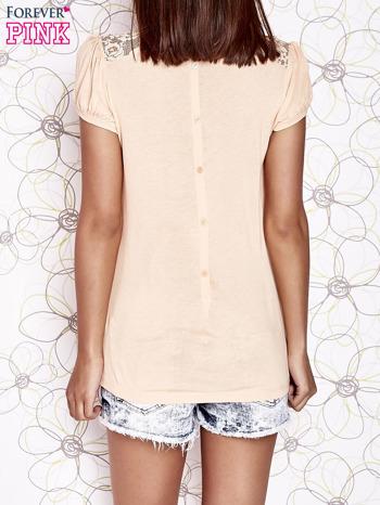 Jasnopomarańczowy t-shirt z ażurowym motywem                                  zdj.                                  2