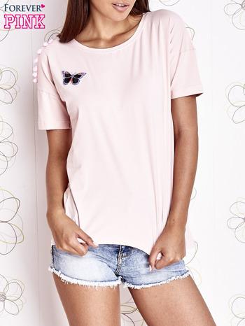 Jasnoróżowy t-shirt z naszywką motyla i pomponikami