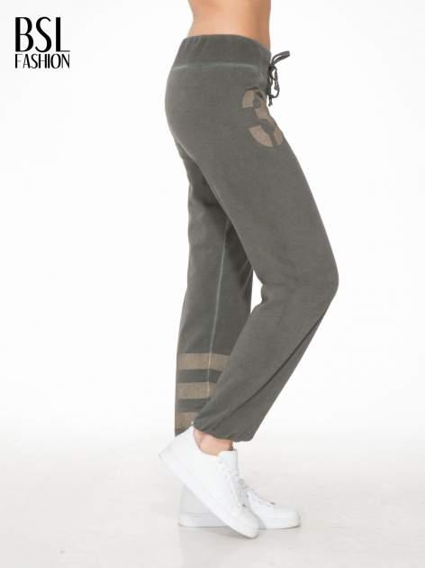 Khaki dresowe spodnie damskie z numerkiem i paskami na nogawkach                                  zdj.                                  3