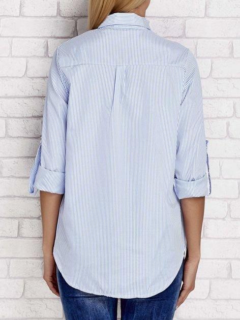 Niebieska koszula z kwiatową naszywką