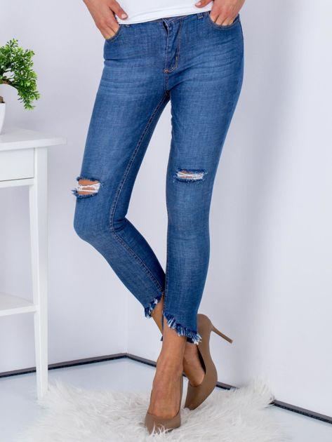 Niebieskie jeansy z rozdarciami i wystrzępionymi nogawkami                              zdj.                              1