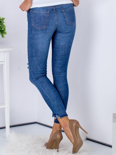 Niebieskie jeansy z rozdarciami i wystrzępionymi nogawkami                                  zdj.                                  2