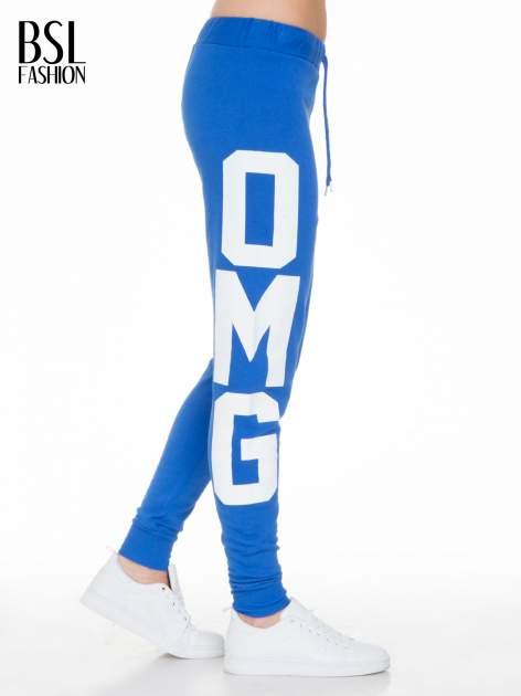 Niebieskie spodnie dresowe z nadrukiem OMG z boku nogawek                                  zdj.                                  3