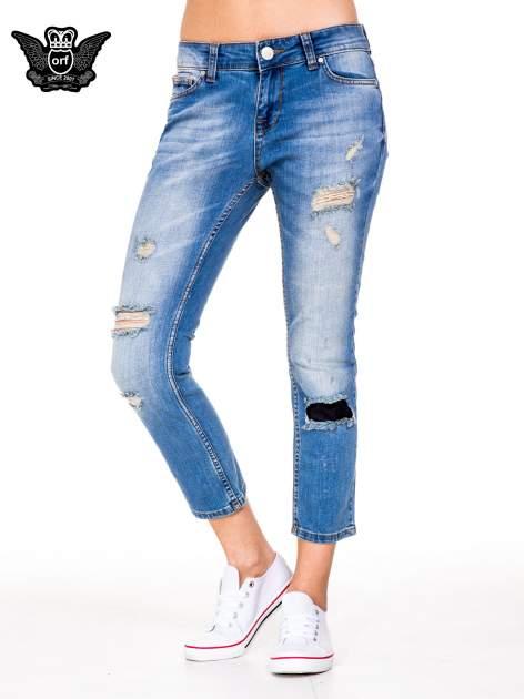 Niebieskie spodnie jeansowe rurki 7/8 z łatą i dziurami