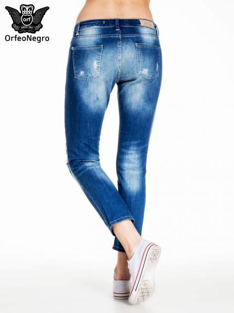 Niebieskie spodnie jeansowe rurki z dziurami na kolanach                                  zdj.                                  2