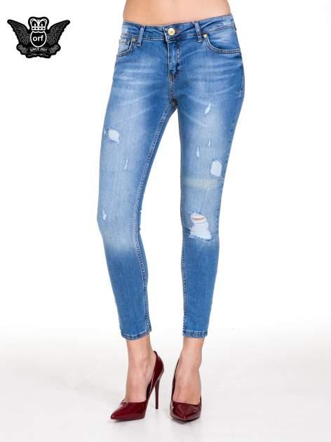 Niebieskie spodnie jeansowe z cieniowaną nogawką z przetarciami                                  zdj.                                  1