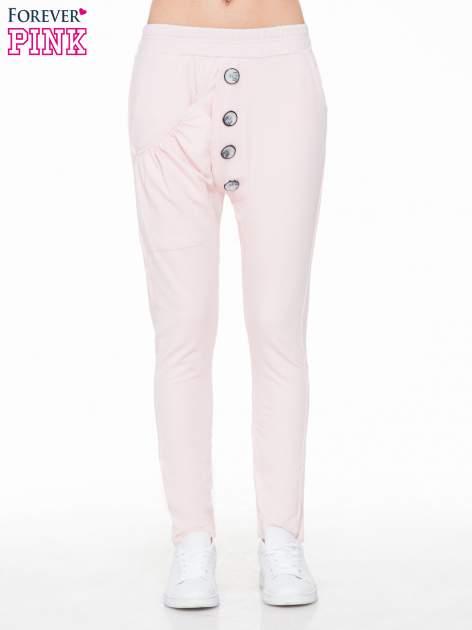 Różowe dresowe spodnie baggy z guzikami i ozdobnymi kieszonkami