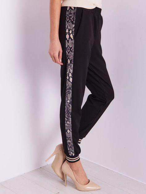 SCANDEZZA Czarne spodnie z wężowym lampasem                              zdj.                              1