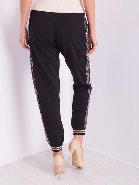Czarne spodnie z wężowym lampasem                              zdj.                              10