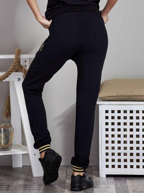 Spodnie dresowe czarne z błyszczącymi lampasami                               zdj.                              2