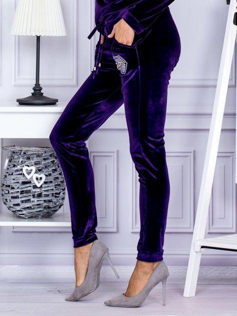 Spodnie dresowe welurowe z błyszczącymi kamyczkami fioletowe                              zdj.                              3