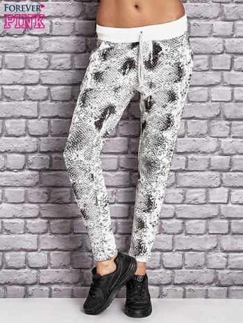 Spodnie dresowe z brokatową aplikacją i nadrukiem ecru                                  zdj.                                  1