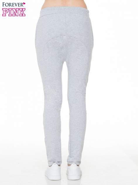 Szare spodnie dresowe typu baggy z naszywkami                                  zdj.                                  4
