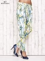 Biało-niebieskie lejące spodnie z kolorowymi paskami                                  zdj.                                  1