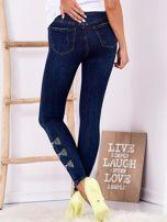Ciemnoniebieskie jeansowe rurki z kokardkami z dżetów                                  zdj.                                  2